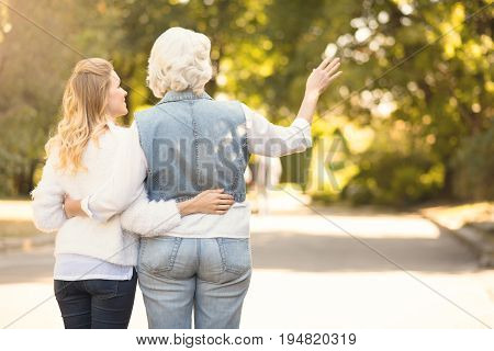 Always hug your parents. Inspiring greyish aging woman enjoying the sunny weather outdoors while expressing joy and hugging mature daughter