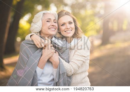 Cherishing family picnic. Mature amused smiling woman enjoying picnic and expressing joy while covering with blanket and hugging aged parent