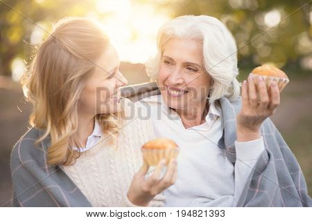 Enjoying peaceful life. Charming delightful young woman enjoying picnic and eating cupcake while covering with blanket and hugging retired mother