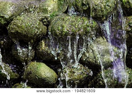 Water running off green algae covered rocks. Waterfall in close up. Natural world textured background image.