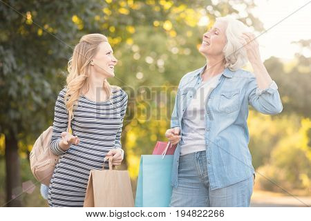 Demonstrating my charisma. Joyful artistic old woman walking in the park while expressing delight and enjoying purchases with pregnant daughter