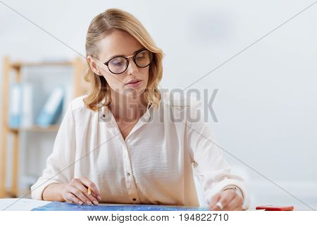 Full of enthusiasm. Involved charming beautiful woman working on the engineering project and analyzing engineering drawing while sitting in the office and expressing attention