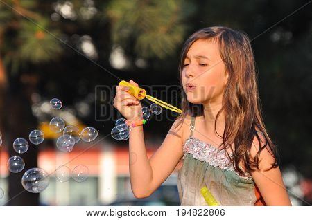 Adorable girl blowing soap bubbles in summer park. Girl play in park and blowing soap bubbles