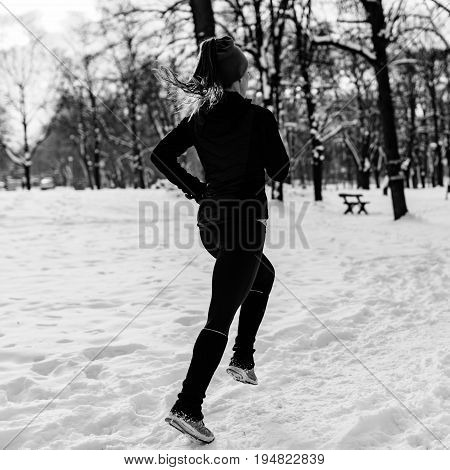 Female Athlete Jogging In Park In Winter, Black And White Image