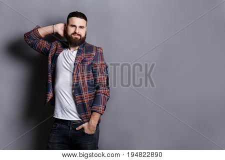 Handsome bearded hipster touching his hair. Young confident guy in checkered jacket in relaxed pose, gray studio background. Flirt, seduction concept