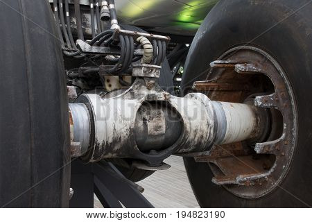 Close Up Of Airplane Wheel And Shaft. Huge Airplane Tyre With Shaft And Landing Gear Of Plane Under