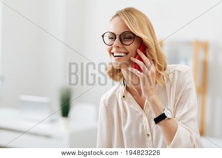 Happy to hear you. Smiling delighted charismatic woman working on the project while using electronic gadget in the office and enjoying conversation