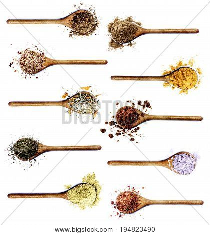 Collection of Various Spices in Wooden Spoons: Coriander Dried Paprika Salt with Chili and Petals Thyme Cumin and Curry Powders Dried Chili and Kosher Salt isolated on White background