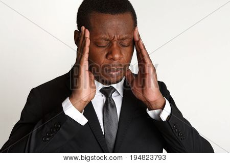 Depressed businessman having headache closeup. Young african american man feeling stressed, touching his head. Stress, failure, frustration concept