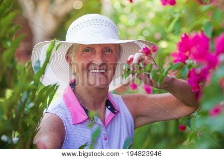 elserly woman happy in garden with sun hat