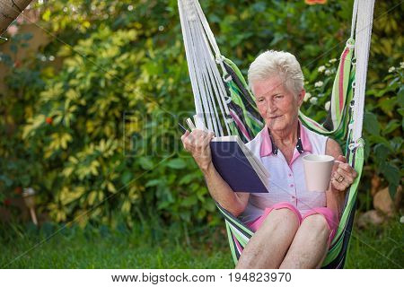 retired healthy senior woman relaxing in garden with book