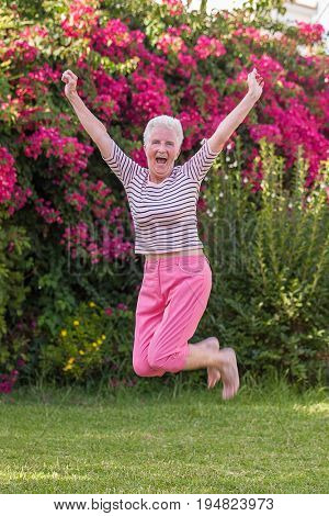 fit healthy happy active senior woman jumping