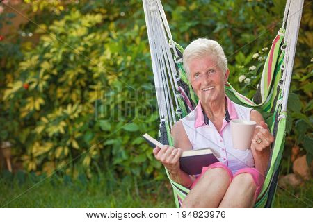 happy pensioner reading in garden swing