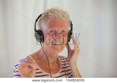 senior woman listening to music wearing headphones.
