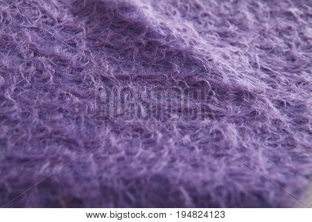 Texture of purple angora woolen cloth. Plush fabric for making toys. Fleecy soft warm material close up
