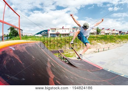 Young boy doing a trick with a jump on the ramp in the skatepark. Photo with a place for copy-space