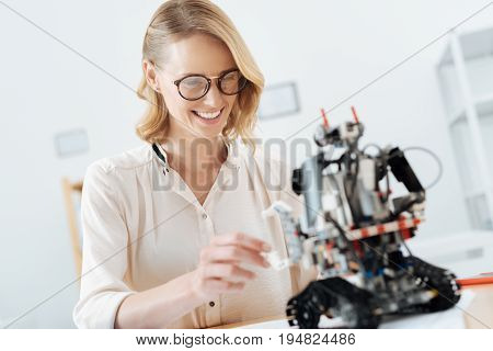 Enjoying epoch of high tech technologies. Smiling skilled optimistic engineer working in the office while looking at the electronic robot and testing the device