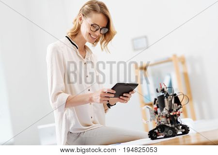 On my way to new tech discovery . Professional smart cheerful engineer working in the lab and using tablet while collaborating with the electronic robot and expressing happiness