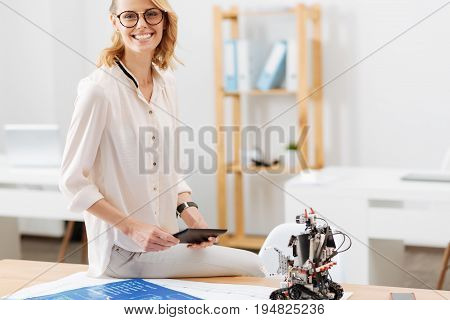 Full of happy emotions. Cheerful intelligent skillful engineer working in the office and using electronic gadgets while expressing joy and working on the project