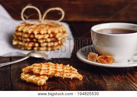 Breakfast with Waffles Stack on Napkin, White Cup of Tea and Pieces of Waffle on Wooden Surface.