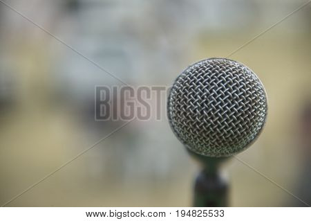 Detail of a microphone for singing taken in front view (view of the singer) with the background completely blurred. Useful as a graphical resource.