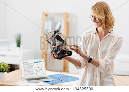 Lets become friends. Inventive skilled clever technology specialist working in the office and holding futuristic little robot while working on the science project