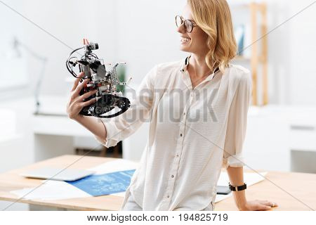 Looking into the future with confidence . Cheerful charming intelligent engineer working in the lab and testing automatic little robot while expressing joy