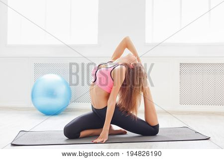 Woman practicing flexible yoga pose. Smiling sporty girl stretching on mat in gym. Healthy lifestyle, weightloss, gymnastics concept