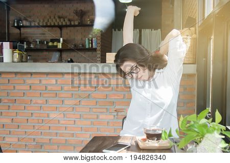 young woman sitting in coffee shop with a smart phone in front of her stretching her arms above her head for relaxing