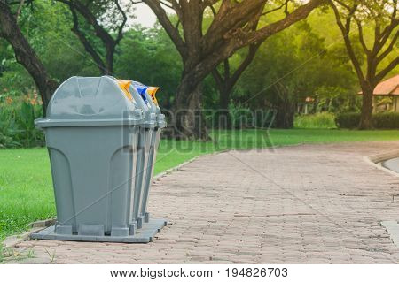 Public recycle bins or segregated waste bins in public park with green natural background.
