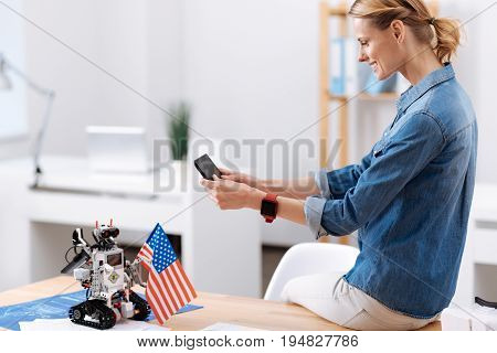 Celebrating Independence Day. Smiling amused skillful woman sitting in the office and taking pictures while using tablet and interacting with electronic robot