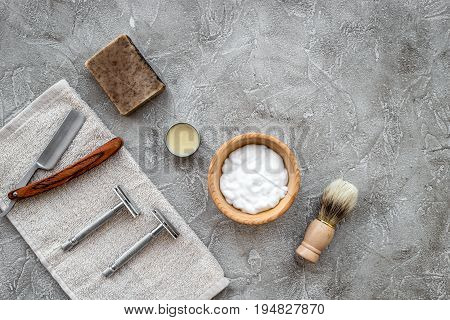 Accessories for shaving. Shaving brush, razor, foam on grey stone table background top view.