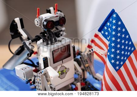 Electronic resident . Funny smart digital robot standing on the table in the laboratory and holding American flag while symbolizing new tech invention