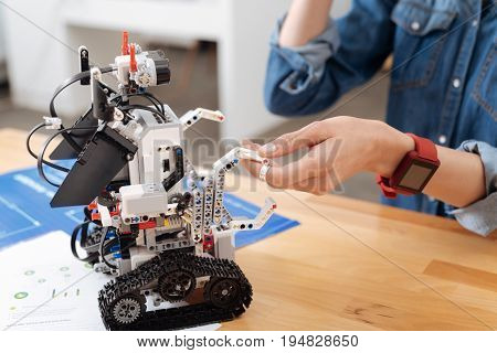 Sharing positivity. Electronic innovative little robot standing on the table in the laboratory and touching humans hand while making friends