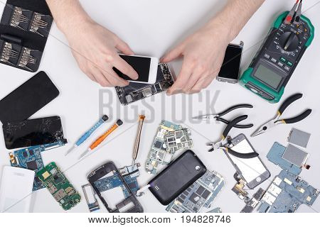 Repairing mobile at service center, smartphone dissasembling and diagnostic, repairman workplace top view