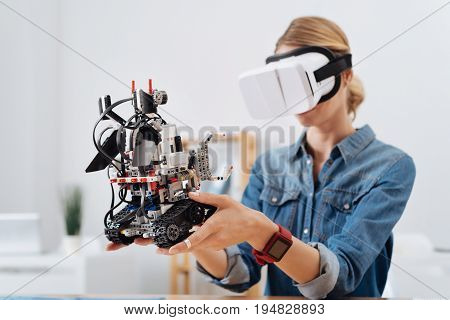 Enjoying another reality. Attentive young charming woman sitting in the lab and testing visual reality glasses while holding automatic robot