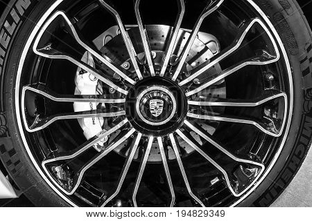 STUTTGART GERMANY - MARCH 17 2016: Wheel and brake system of a mid-engined plug-in hybrid sports car Porsche 918 Spyder 2015. Close-up. Black and white. Europe's greatest classic car exhibition