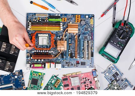 Maintenance support and repairing service concept. Technician upgrade of computer top view. Renovation microchip component in motherboard.