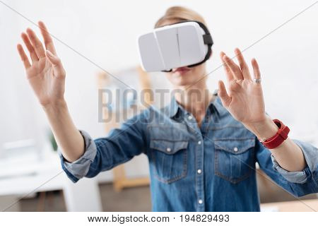 Facing new opportunities . Attentive young curious woman taking part in the tech experiment and testing visual reality headset while expressing interest