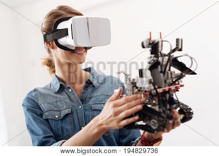 Enjoying realistic images. Smiling optimistic upbeat woman using visual reality headset while holding little electronic robot and expressing joy