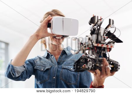 Enjoying new sensations. Smiling glad pleasant woman using visual reality headset while holding little smart robot and expressing positivity