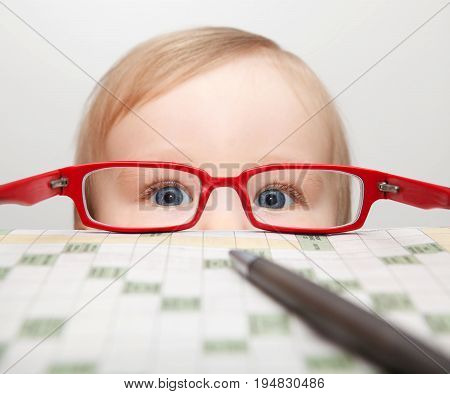 small child with blue eyes,ballpoint,crossword and red glasses