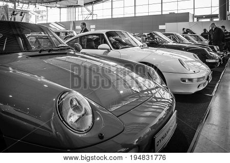 STUTTGART GERMANY - MARCH 17 2016: Various models of Porsche sports cars stand in a row. Black and white. Europe's greatest classic car exhibition