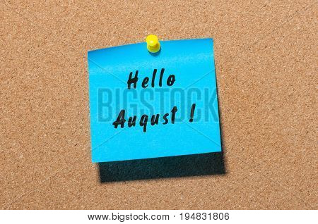 Hello August on blue sticker pinned to cork noticeboard.