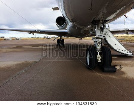 This photo consists of a landing gear of a Private Jet which is taken from the front of the airplane. Also contains a good view of the wing and the jet engine. With its door open, it urges you too come on board!!