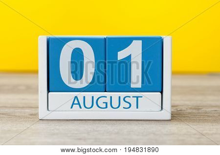 August 1st. Image of august 1, close-up wooden color calendar on yellow background. Summer day.