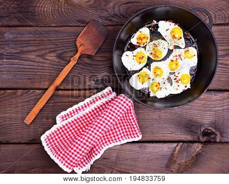 Fried quail eggs in a black frying pan with a handle and a red napkin next to a wooden scapula top view