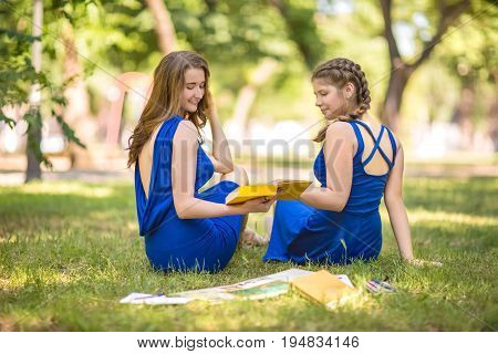 Beautiful girls with light brown hair and in blue dresses are sitting on the grass in the park and reading books. Two gorgeous and beautiful girls with books have fun in a park. Beautiful girls-students in blue dresses sit in the park and read books.