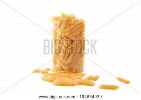 Raw and bright yellow pasta in a huge transparent glass, isolated on a white background. Typical Italian food pasta in a jar. Fettuccine noodles in a glass.
