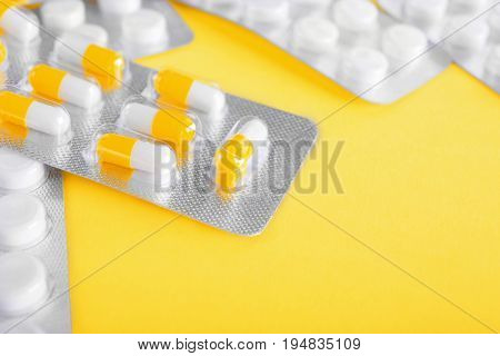 A bright colorful set of multiple painkillers, antibiotics in a few packs. Pills on a light spacious yellow background. Drugs, tablets in capsules. Medicinal chemistry.